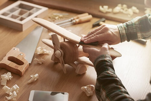 Using the sandpaper on a wood airplane